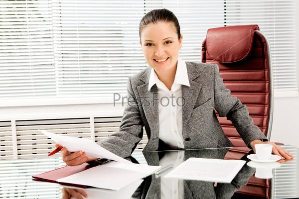 Девушка с документами в руках сидит за столом в офисе и улыбается