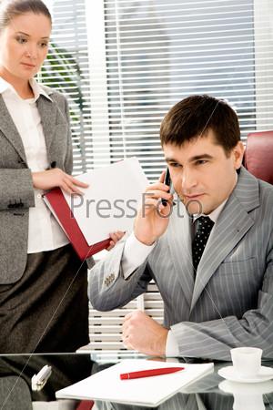 Уверенный начальник разговаривает по телефону, рядом стоит секретарь