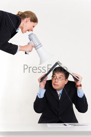 Деловая женщина кричит на мужчину спрятавшегося под ноутбуком
