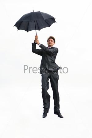 Мужчина в костюме с раскрытым зонтом висит в воздухе