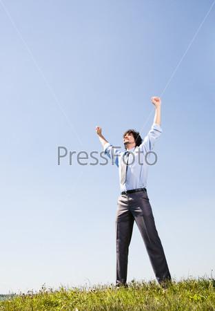 Деловой мужчина стоит на поляне подняв руки к голубому небу