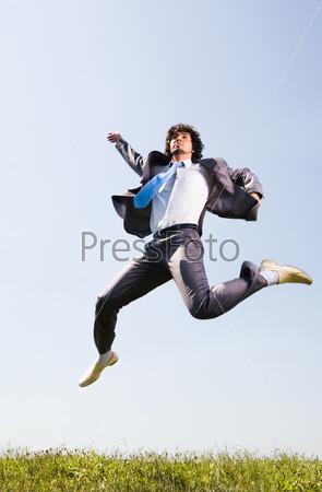 Бизнесмен резвится на зеленой поляне