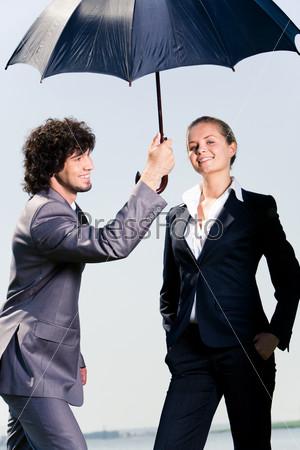 Мужчина прячет женщину от дождя под зонтом