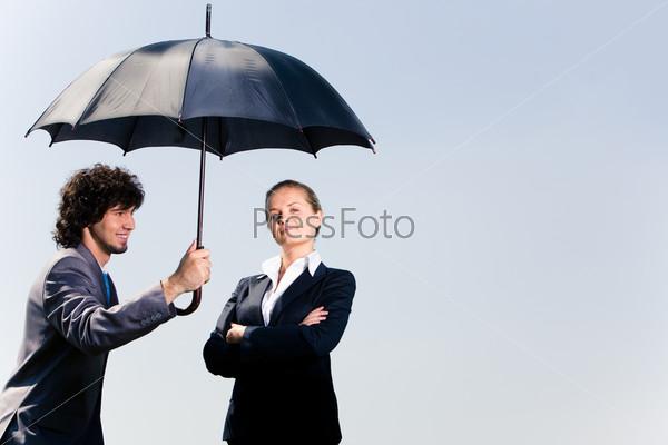 Молодой человек прикрывает зонтом успешную деловую женщину