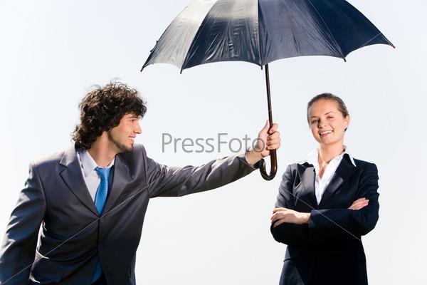 Мужчина держит зонт в вытянутой руке над миловидной девушкой