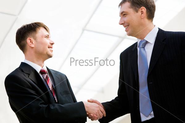 Фотография на тему Два бизнесмена пожимают друг другу руки после заглючения выгодной сделки