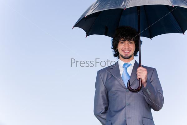 Успешный бизнесмен в костюме стоит под зонтом и улыбается