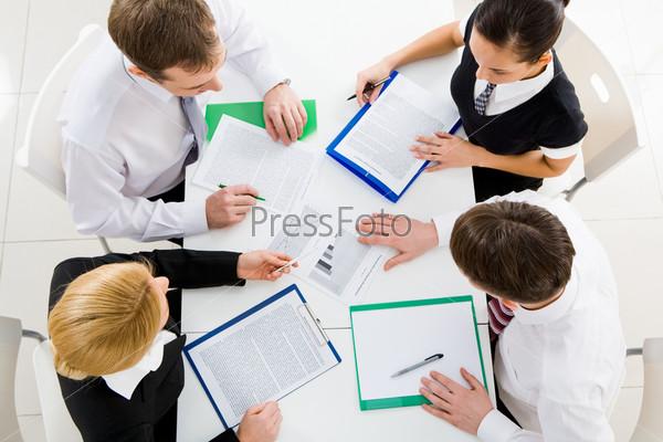Вид сверху бизнес команды за рабочим столом во время обсуждения новых планов