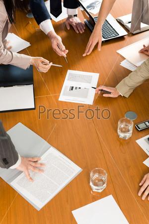 Люди склонились над документами лежащими на полу