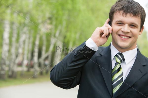 Привлекательный мужчина разговаривает по телефону на улице и улыбается