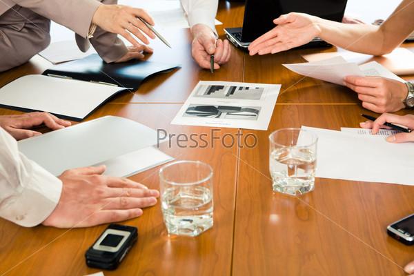 Несколько пар рук бизнесменов совместно работающих на семинаре