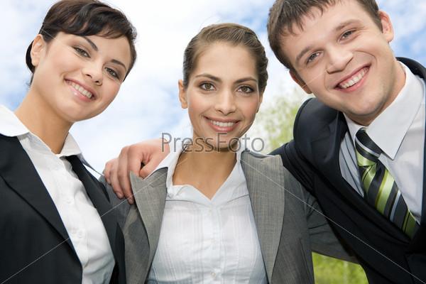 Дружный коллектив стоит обнявшись с улыбками на природе