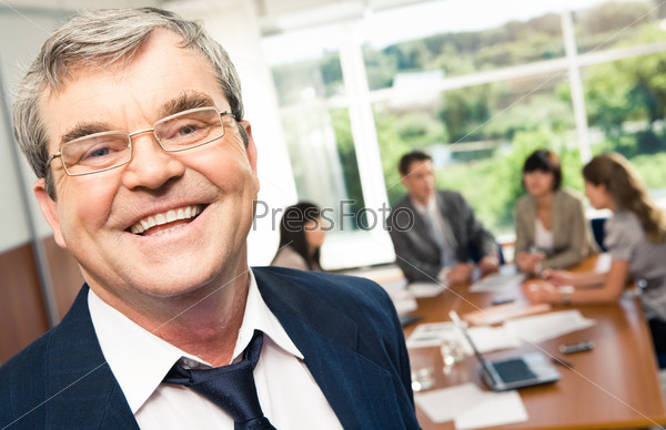 Солидный пожилой бизнесмен смеется глядя в камеру на фоне подчиненных за столом