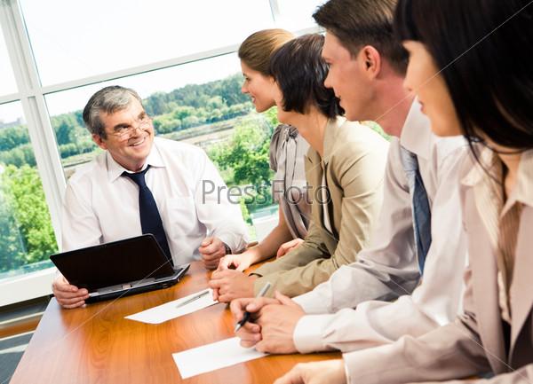 Фотография на тему Генеральный директор выслушивает отчеты своих сотрудников в своем кабинете