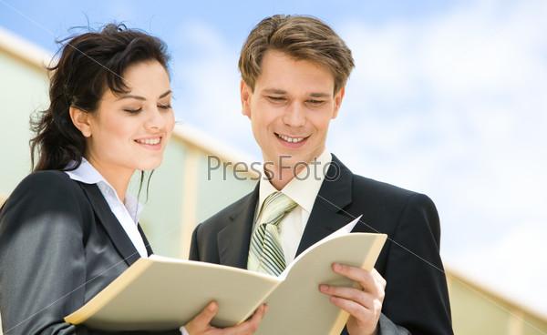 Деловые молодые люди смотрят в папку с докуменами на улице
