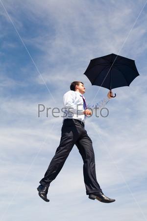 Современный молодой человек идет по воздуху держа в руках зонт