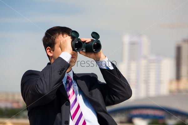 Бизнесмен с биноклем смотрит вдаль на фоне города