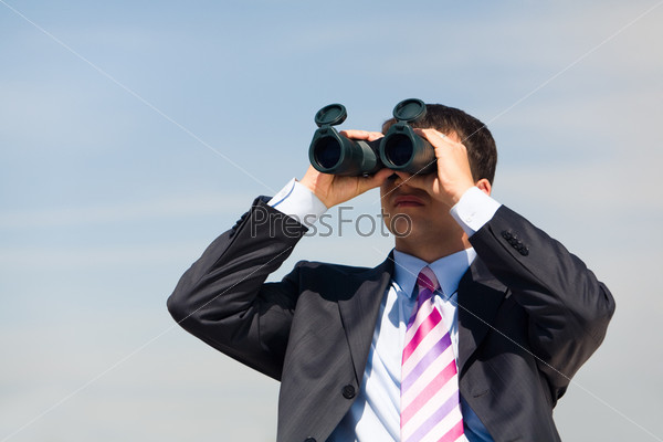Директор смотрит в бинокль на фоне неба