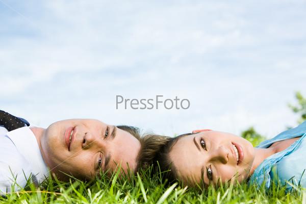Крупный план лиц молодых людей лежащих на траве