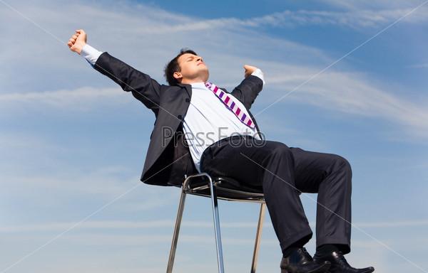 Фотография на тему Директор отдыхает на стуле на фоне голубого неба