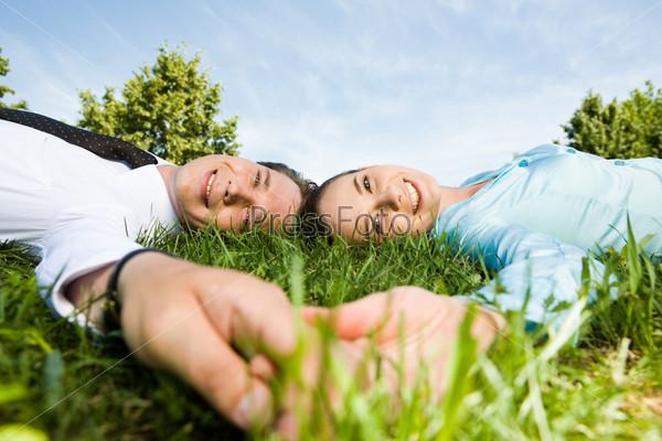 Два менеджера лежат на траве держась за руки
