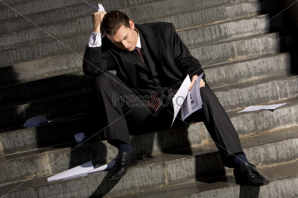 Грустный молодой человек с бумагами в руках сидит на ступеньке и не знает что делать