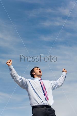 Деловой мужчина кричит подняв руки к небу