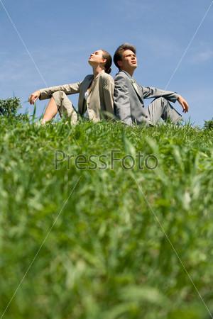 Молодая пара сидит на поляне спиной друг к другу