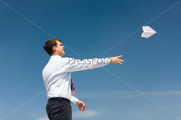 Мужчина в белой рубашке запускает в небо бумажный самолетик