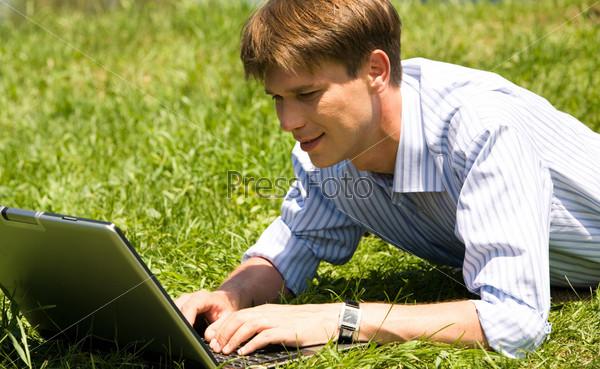 Привлекательный молодой челове работает за ноутбуком лежа на зеленой поляне