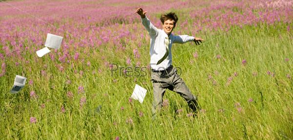 Мужчина бежит по цветущему лугу и разбрасывает документы