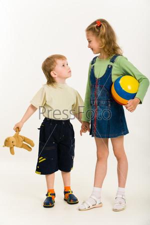 Фотография на тему Девочка держит за руку своего младшего брата