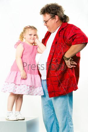 Хорошенькая девочка в розовом платье облокотилась на папин живот