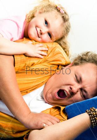 Папа зевает лежа на диване, сверху на нем лежит очаровательная дочь