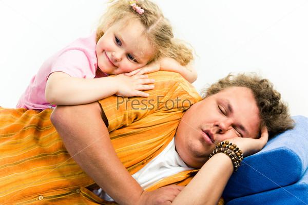 Папа спит на диване, сверху на него прилегла дочь