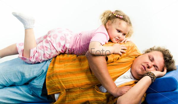 Дочка лежит и смотрит на спящего папу на диване