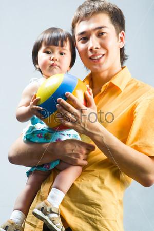 Папа держит свою дочь на руках и улыбается