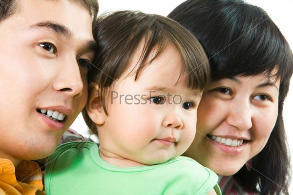 Мама, папа и дочь вместе улыбаются глядя в сторону