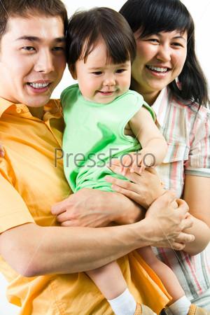 Счастливый папа держит на руках дочь, рядом стоит мама и улыбается