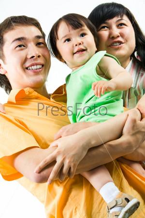 Счастливая семья с девочкой на руках смотрит в сторону