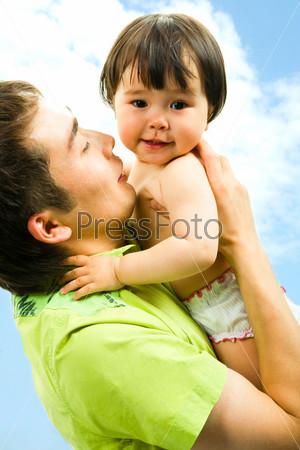 Девочка сидит на руках у папы и улыбается на фоне голубого неба