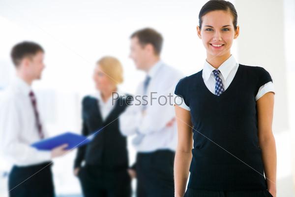 Привлекательная бизнес-леди улыбается на фоне коллег