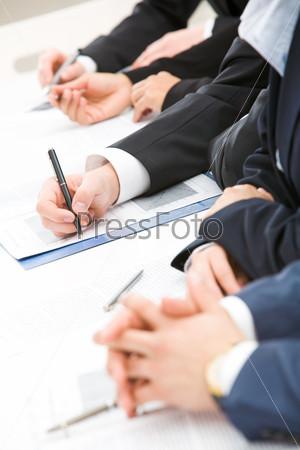 Ряд из рук, конспектирующих что-то на листах бумаги