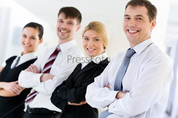 Бизнес партнеры стоят в ряду скрестив руки и улыбаются