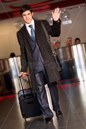 Привлекательный бизнесмен идет в аэропорту и машет рукой на прощание
