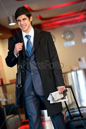 Счастливый молодой человек в костюме и пальто с чемоданом и газетой в руке стоит в аэропорту