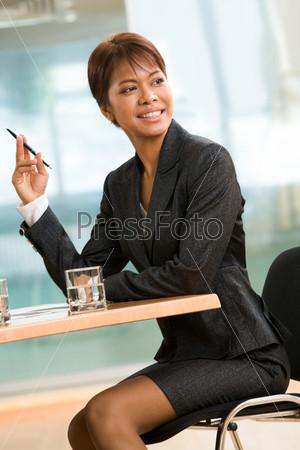 Темнокожая бизнес леди сидит за столом во время конференции и смотрит в сторону