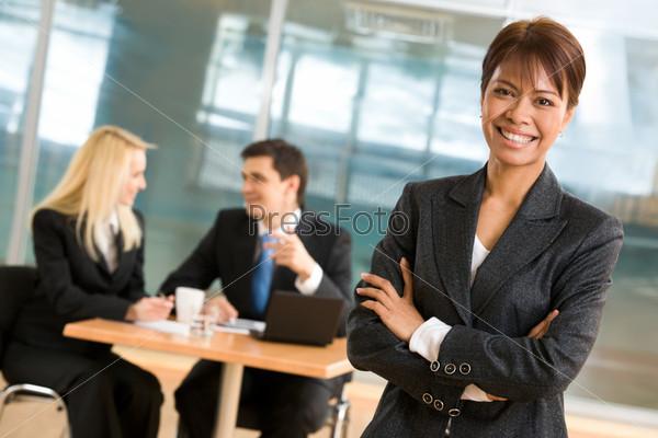Бизнес леди стоит на фоне общающихся сотрудников