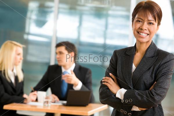 Уверенная в себе бизнес леди стоит на фоне коллег