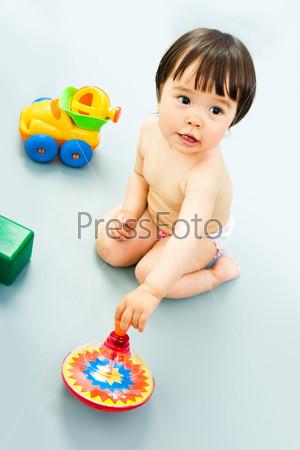 Маленькая девочка сидит на полу в окружении игрушек